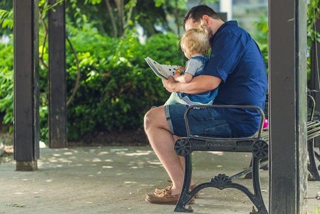 Padre e hijo sentado en regazo leyendo