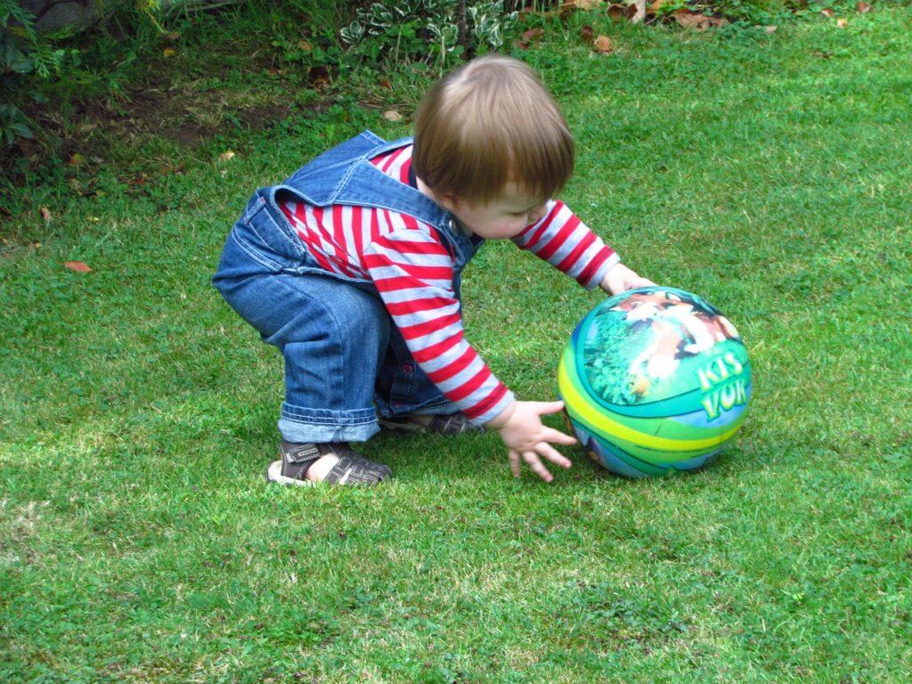 niño con pelota en el cesped