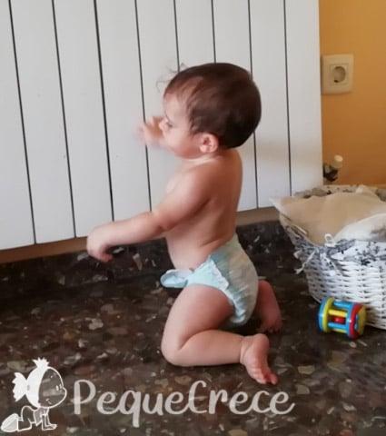 bebe en postura de rodillas con radiador detras
