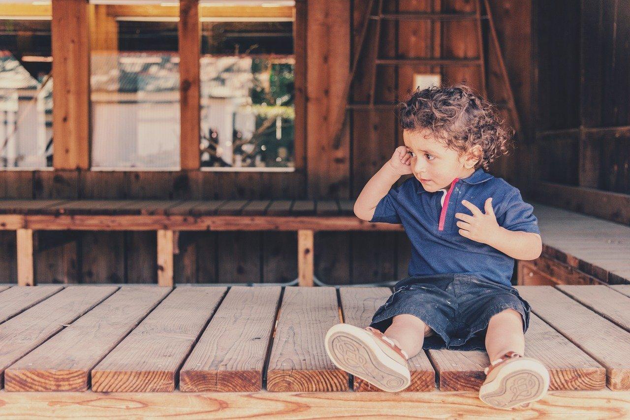 niño sentado en porche de madera