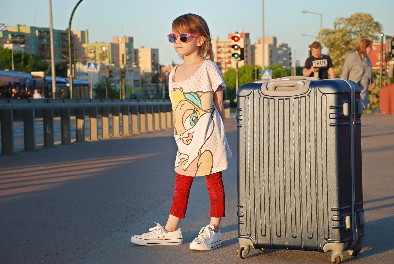 niña con maleta y ropa de mayor
